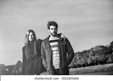 Young couple of pretty cute girl and bearded man hipster outdoors in park on autumn day on natural blue sky background near water