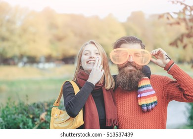 Young couple of pretty girl and bearded man hipster with funny orange eyeglasses outdoors in park on autumn day on natural background