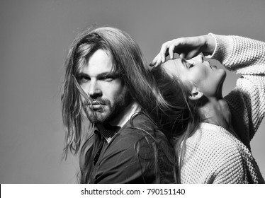 Young couple of pretty girl or beautiful sexy woman with long messy hair on handsome man head and face on grey background