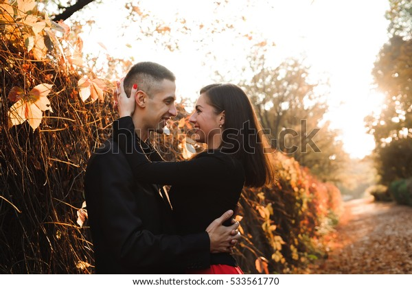 Young couple of pretty girl and man walk outdoors in park on autumn day on natural background