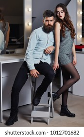 Young couple of pretty sexy woman in gray dress has slim body and handsome bearded man with long beard in shirt near big mirror in hairdressing salon or barbershop. Beautiful fashion couple. Hipster.