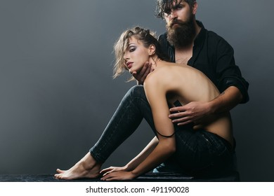 young couple of pretty sexy woman in black jeans and bra has slim body and handsome bearded man with long beard in shirt on grey background, copy space
