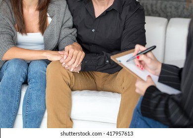 Young couple with a problem to consult a psychologist closeup, therapy, holding each other hand