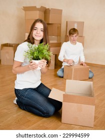 Young couple puts things in cardboard boxes for moving into a new home