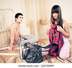 Young couple in quarrel. The girl collects things