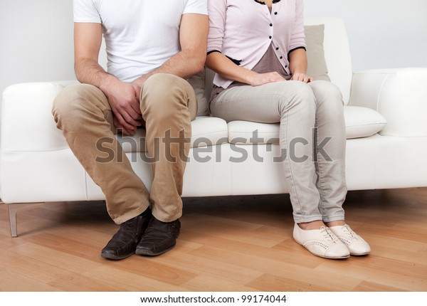Young couple in quarrel at home. Sitting on the couch