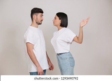 Young couple quarreling at home. Girlfriend giving slap to her boyfriend isolated on white background.