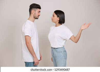 Young couple quarreling at home. Woman giving slap to her husband isolated on white background.