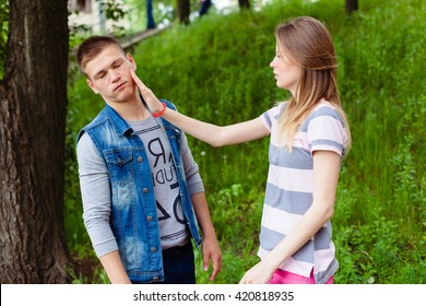 Young couple quarreling outdoors. angry woman girl giving slap to her boyfriend. slapping across