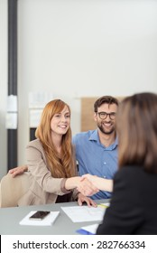 Young couple reaching an agreement with a broker or agent as the wife shakes her hand watched by a smiling husband