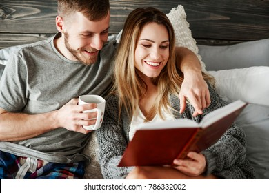 Young couple reading book at bedroom