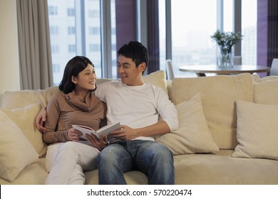 Young couple reading a book together on a sofa