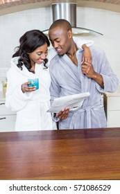 Young couple reading newspaper in the kitchen