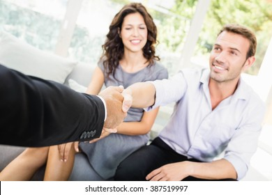 Young couple ready to buy new house shaking hands with estate-agent
