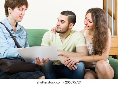 Young couple and real estate agent signing agreement at home