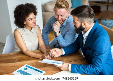 Young couple with a real estate agent. Buying new house.