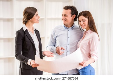 Young couple with realtor are watching the plan of a house.