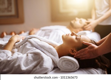 Young couple receiving head massage at beauty spa