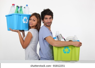 Young couple recycling bottles