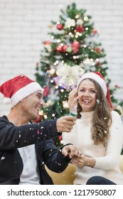 Young couple in red hat sitting on sofa between christmas trees and play pull the pop up funny  paper shoot together. Concept for happiness and sharing time in christmas and new year festival