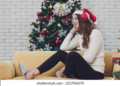 Young couple in red hat sitting on sofa between christmas trees and listening to music with headphone in front of hugh christmas tree. Concept for good time and happiness in christmas day.