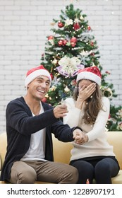 Young couple in red hat sitting on sofa between christmas trees and play pull the pop up funny  paper shoot together. Concept for happiness and sharing time in christmas and new year festival.