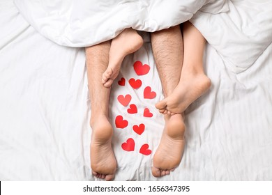 Young couple with red hearts lying in bed, top view
