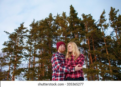 young couple in red shirt standing in an embrace in a winter forest