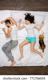 Young couple relaxation on the bed top view with a dog sleeping