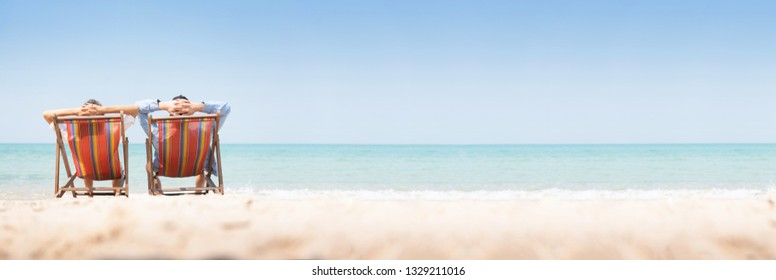 Young couple relaxing with arms up on chair beach during Summer Vacation together. Panoramic, Banner, Copy space.