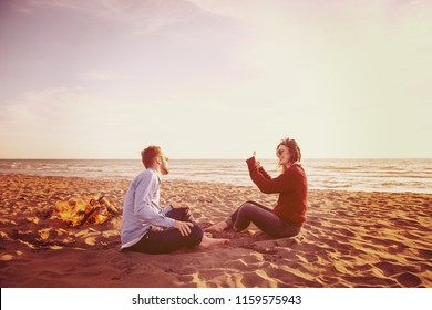 Young Couple Relaxing By The Fire, Drinking A Beer Or A Drink From The Bottle on the beach at autumn day filter