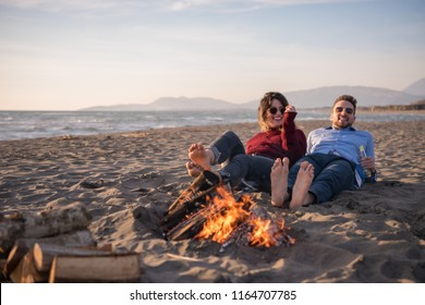 Young Couple Relaxing By The Fire, Drinking A Beer Or A Drink From The Bottle on the beach at autumn day