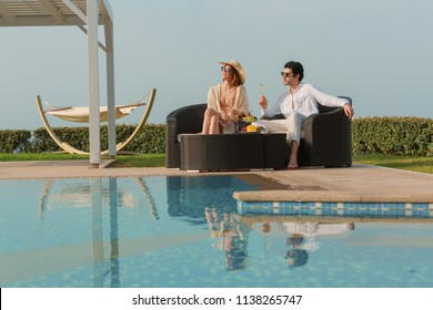 Young couple relaxing by the swimming pool, drinking wine