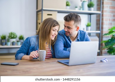 Young couple relaxing drinking a coffee and using the computer laptop around cardboard boxes, very happy moving to a new house
