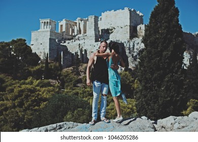 Young couple is relaxing and enjoying the view of the city. Toned picture. Happy family couple. Fashion photo. City background. Love story. Man and woman posing. Summer time. Summer. Couple in love.