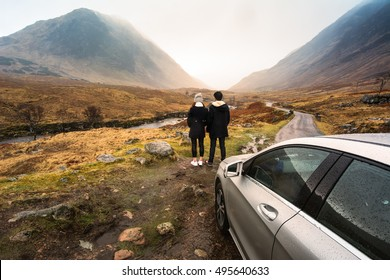 Young couple is relaxing and enjoying the view of mountain filming location of Skyfall Movies After The Rain, Glencoe valley, Scotland.