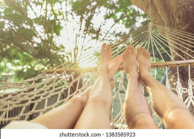 Young couple relaxing in hammock enjoying summer holiday vacation