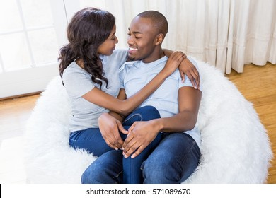 Young couple relaxing on a bean bag in the living room