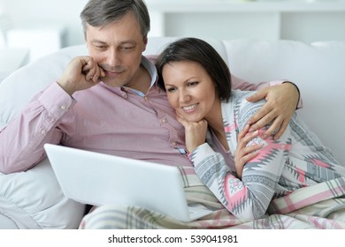 young couple relaxing on the couch with a computer