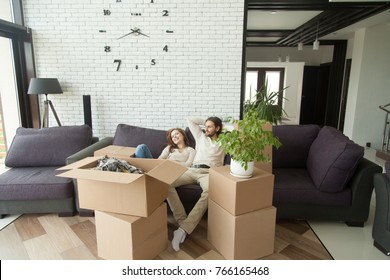 Young couple relaxing on couch just moved into new home with cardboard boxes, happy man and woman packed belongings sitting on sofa in living room, moving delivery service and relocation concept