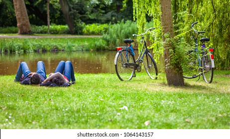 Young couple relaxing on the grass in public park after a bike ride, Vondelpark, Amsterdam, Holland