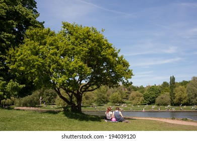 A young couple relaxing on the grass in Hampstead Heath during the summer months in London.