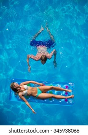 Young Couple relaxing on a lilo mattress at the swimming pool
