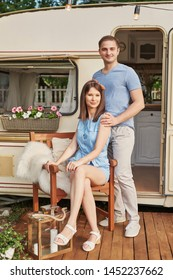 young couple relaxing on a picnic in the summer near the trailer on wheels