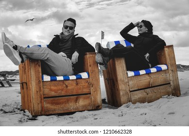 Young couple relaxing on sand baskets at the beach of the Northern Germany island Amrum.