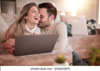 Young couple relaxing on sofa with laptop.Love,happiness,people and fun concept.