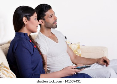 young couple relaxing on the sofa in tv lounge, Indian couple watching movie