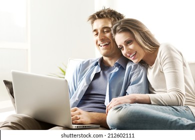 Young couple relaxing on sofa with laptop in the living room.