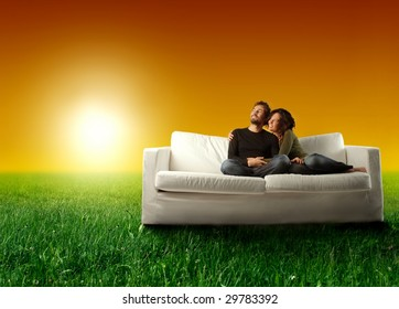 young couple relaxing on a sofa in a grass field