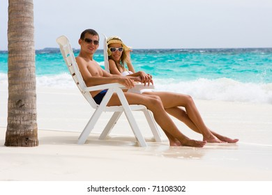 Young couple is relaxing on a tropical beach under a palm